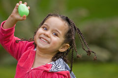 Found an Easter Egg. Young happy girl holding up a green plastic Easter egg Stock Photo