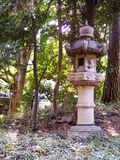 Old Japanese stone lantern in amongst trees. Found in the estate grounds of a Japanese castle in Tokyo, this antique stone lantern has various animals carved on Royalty Free Stock Image
