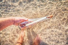 Message in a bottle. Found a message in a bottle at beach in sea water. Man hold bottle in hand Royalty Free Stock Photo