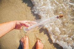 Message in a bottle. Found a message in a bottle at beach in sea water. Man hold bottle in hand Stock Photos