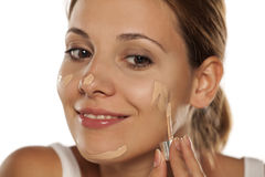 Foundation apply. Young beautiful woman applying foundation on her face royalty free stock images