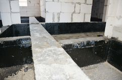 Foundation bitumen waterproofing. Building house construction with waterproofing spray-on tar. Photo stock image