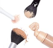 Foundation, concealer pencil and powder with makeup brushes Royalty Free Stock Photos