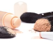 Foundation, concealer pencil and powder with makeup brushes stock image