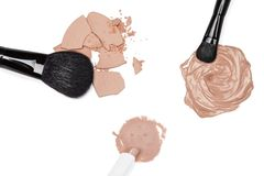 Foundation, concealer and powder with makeup brushes. Foundation, concealer and crushed cosmetic powder with makeup brushes on white background Royalty Free Stock Image