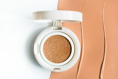 Foundation cushion on half of the surface of a tonal base. Smeared on a white background stock image