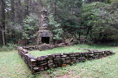 Foundation for an historic pioneer house. A picture of a stone base and chimney for a home in the forest Royalty Free Stock Photography
