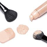 Foundation with makeup brushes and cosmetic sponge stock images