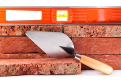 Foundation of the new house. Red clay bricks, trowel and level Stock Images