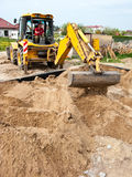 Foundation sand filling. New house building process - filling the foundations with sand with a digger machine Royalty Free Stock Photo