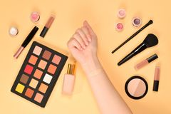 Foundation on woman hand. Professional makeup products with cosmetic beauty products, foundation, lipstick,  eye shadows, brushes. And tools. Top view royalty free stock images