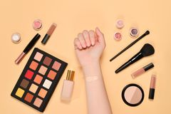 Foundation on woman hand. Professional makeup products with cosmetic beauty products, foundation, lipstick,  eye shadows, brushes. And tools. Top view royalty free stock photography