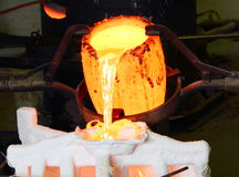 Foundry Molten Metal Pour. Pouring hot liquid molten metal into a mold. Red hot, Horizontal format Stock Photos