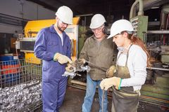 Foundry team working in cooperation. Making quality control on workpieces royalty free stock image