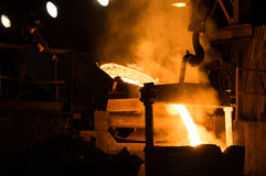 Foundry Worker Watching Hot Liquid Metal Flow Stock Photography