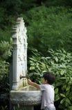Маленький ребенок играя с водой от fountai классики стиля тахты Стоковое Изображение RF