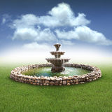 Fountain. A fountain with a rock base in a grassy field with a cloudy background. Concept for a magic or fountain of youth stock photography