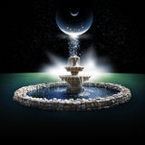 Fountain. A fountain with a rock base under a celestial event in a starry night sky stock photo