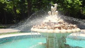 Fountain with angels statue in a sea garden park with grass and trees around it in Varna, Bulgaria.  stock footage