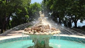 Fountain with angels statue in a sea garden park with grass and trees around it in Varna, Bulgaria.  stock video