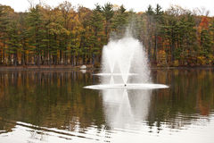 Fountain. Autumn forest lake with a fountain and a reflection Royalty Free Stock Images