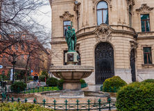 Fountain on the background the facade of Metropolitan Ervin Szabo Library in Budapest. BUDAPEST, HUNGARY - FEBRUARY 21, 2016: Fountain on the background the Royalty Free Stock Photography