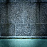 Fountain of blue water and stone wall Royalty Free Stock Image