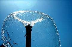 Fountain bubble. A fountain back lit by the sun stock photo