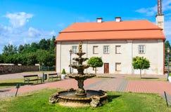 Fountain and building of the former barn. Catholic church.Liskiava. Lithuania Stock Photos