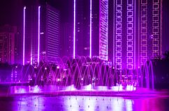 Fountain, building with Ultra Violet decorative lights. Night modern building with decorative lights by the lake,and foreground is a Ultra Violet fountain royalty free stock images