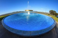 A fountain in a circular pool, taken with a fisheye lens royalty free stock photo