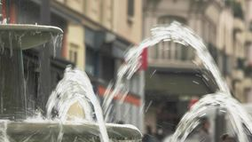 Fountain in the city street. People walk near building. Stop at picturesque place. Visiting Europe in summer stock footage
