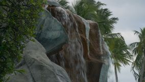 Fountain close-up with palm trees in the background. 4k stock footage