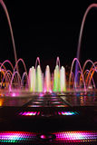 Fountain with colorful illuminations at night Stock Images