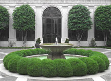 Fountain in a courtyard. Water fountain in the middle of an enclosed courtyard with green shrubs Royalty Free Stock Photo