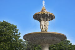 Fountain decorated by marble statues Stock Photos