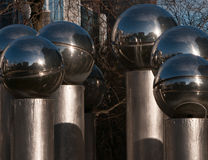 Fountain detail. Six shiny metal orbs on top of a cylindrical metal tube Stock Images
