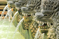 Fountain of dragon statues at Bali hot springs in Indonesia. Row of stone carved dragon fountain statues at Balinese hot springs in Bali, Indonesia stock photos