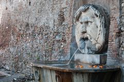 Roman thermal bath. Fountain at the entrance to the orange garden, Aventino district, Romarre. Composed by a Roman thermal bath and the monumental marble mask stock photo