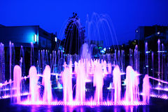 Fountain in the evening city. Fountain illuminated by coloured lamps effect luminous jets and water Stock Photo