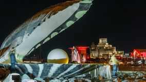 A fountain featuring an oyster with a gigantic pearl inside night timelapse with the Doha skyline behind it