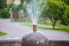 A fountain in the form of a ball with built-in pipes, from which water flows down over the town square, splashing stock image