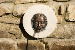 Fountain in the form of iron masks Stock Images
