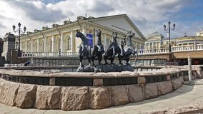 Fountain Four Seasons in Moscow. Moscow, Russia. April 14, 2019 Fountain Four Seasons on Manezhnaya Squares and the building of the central exhibition hall. Text royalty free stock image