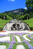 Fountain in the garden of the Linderhof castle in Germany with a view of the Aplen Royalty Free Stock Photo