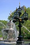 Fountain with Gaslights. City park with splashing fountain and burning gaslights in front Stock Image