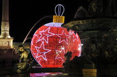 Fountain and a Giant Red Xmas Ball with White Star. Christmas giant ball with red lights and white stars and some details of one of the fountains in Rossio Royalty Free Stock Photography