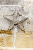 Fountain with gushing. Detail of a public fountain where sgroga a gush of water Stock Photo
