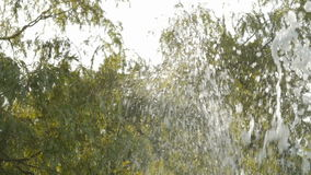 Fountain jet, slow motion. Closeup shot of fragment of fountain. Slow motion,water in rays of light, looking up, tree tops and blue sky in the background stock footage
