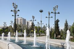 Fountain, lampposts and some living building. Ashkhabad. Turkmenistan royalty free stock photography